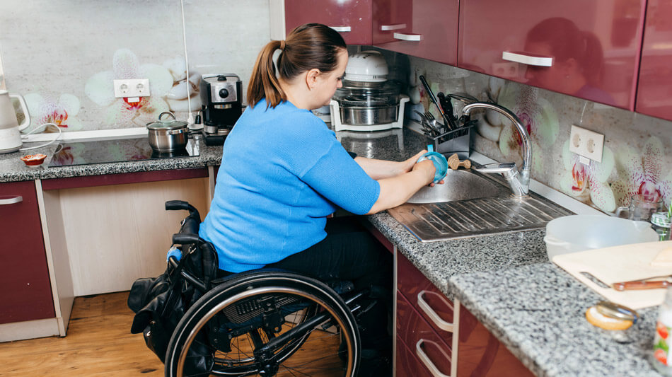 A woman in a wheelchair washing dishes unassisted