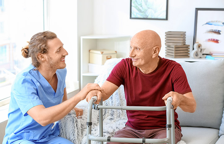 A younger male carer supporting an older man using a walking frame